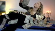 Money flies all around while woman counts the bills video