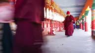 monk and nun walking around prayer wheel in Larung Gar(Larung Five Sciences Buddhist Academy). a famous Lamasery in Seda, Sichuan, China. video