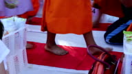 Monks walking on red carpet for receive food offerings video
