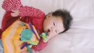 6 months baby girl reading cloth book and teething video