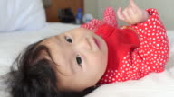 6 months smiling baby girl lying on bed video