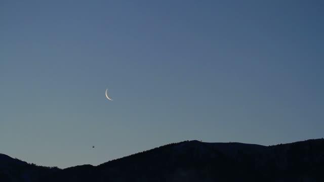 Moon rising over mountain range video