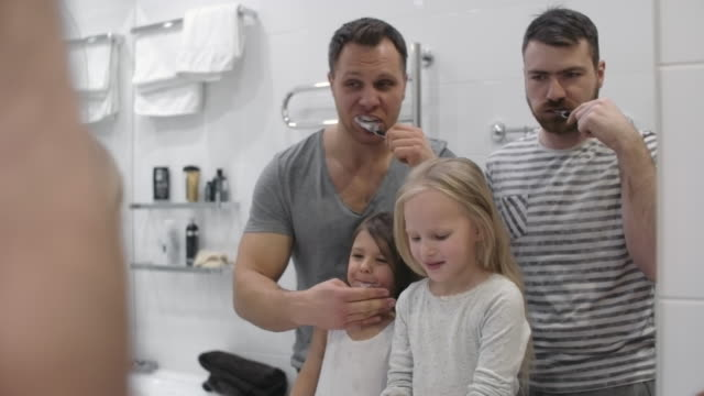 Morning hygiene of same-sex couple and their daughters video