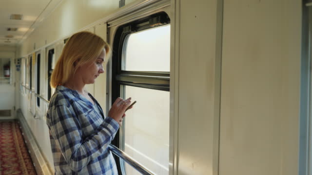 Morning on the road. A woman uses a telephone in a train car, stands by the window video