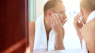Morning regular bathroom scene: young adult man foames his face before shaving video