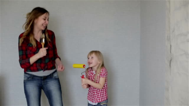 A mother and a small daughter singing and dancing with brushes. video