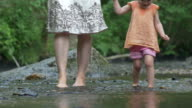 Mother and a young daughter paddle barefoot over rocks video