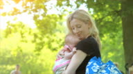 Mother and baby in park summer scene video