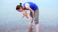 Mother and baby on the beach of the sea video