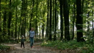 Mother and baby walk on country rural road in forest and then girl run toward the camera video