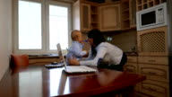 Mother and baby with laptop in the kitchen video