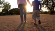 Mother and child holding hands,walking into setting sun,South Africa video