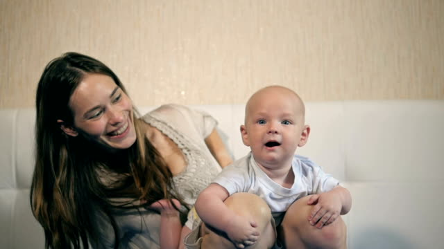 Mother and child on a bed. Mom and baby boy in diaper playing in sunny bedroom. Parent and little kid relaxing at home. Family having fun together video
