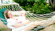 Mother and child resting in hammock video