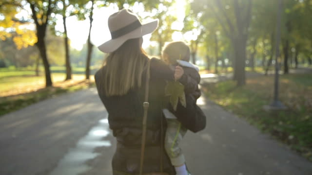 Mother and child walking together in autumn park video