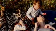 mother and children lie on plaid in field. Slow mo video