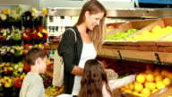 Mother and children picking out fruit in supermarket video