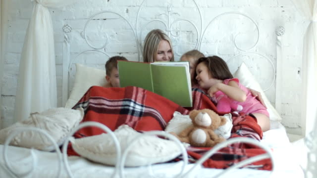 Mother and children reading book video