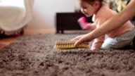 Mother and cute baby girl brushing the rug , baby is learning how to clean and assist her mother video