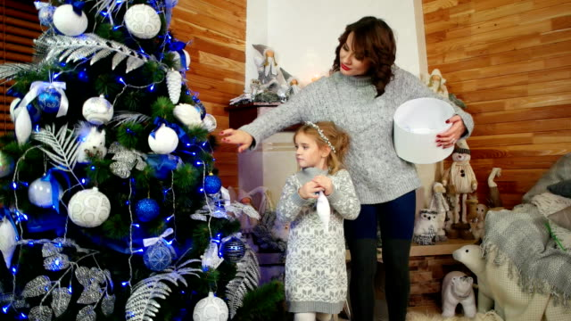 Mother and Daughter are Preparing for the New Year Holiday, Family decorating a Christmas tree, happy family at home in the living room in a cozy atmosphere video