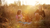 mother and daughter at a picnic at sunset video