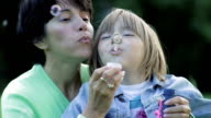 Mother and daughter blowing bubbles video