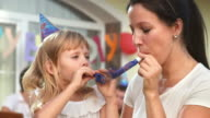 HD: Mother And Daughter Blowing Party Horn Blower video