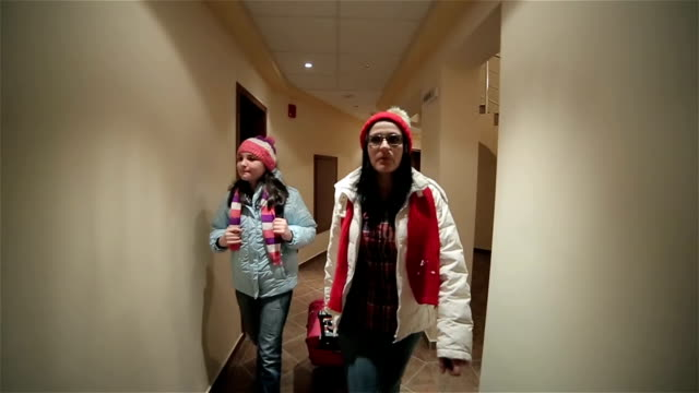 Mother and daughter come to the hotel,winter vacation,camera stabilization shoot video