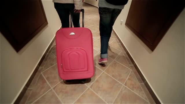 Mother and daughter drag their suitcase in the hotel,camera stabilization shoot video