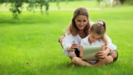 Mother and daughter drawing on grass in park video