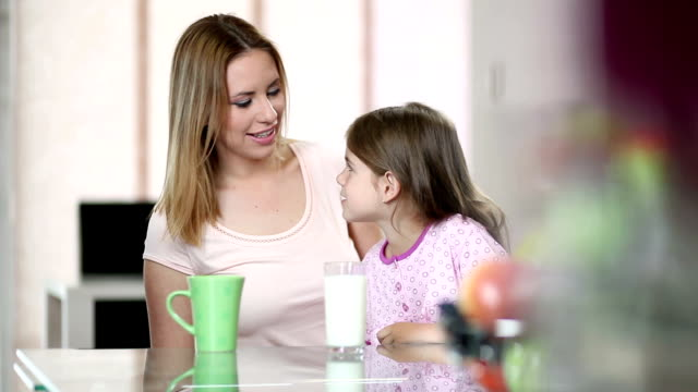 Mother and daughter drinking milk and coffee video