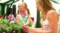Mother And Daughter Growing Plants In Greenhouse video