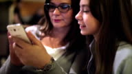 Mother and daughter in a coffee shop using smart phone video
