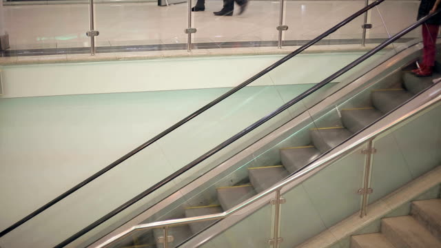 Mother and daughter in a supermarket on the escalator. video