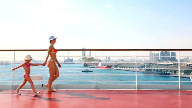 Mother and daughter in bikini walks on deck of ship video