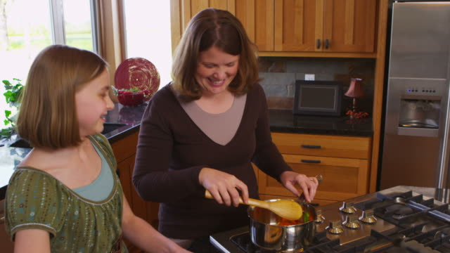 Mother and daughter in kitchen together video