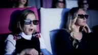Mother and daughter is watching film in a 3d cinema child eating popcorn video
