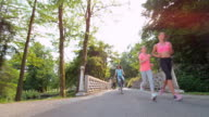 DS Mother and daughter jogging across a bridge in the park video