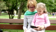 Mother and daughter looking at pictures on mobile phone video