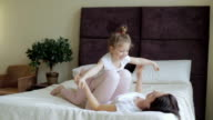 Mother and daughter lying and playing on the bed at home video