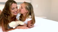 Mother and daughter lying on their bed video
