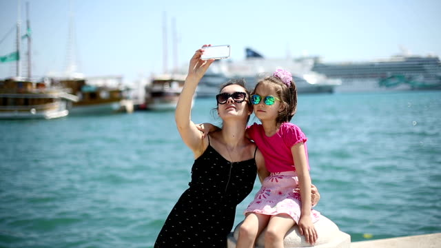 Mother and daughter on vacation photographed in the port. video