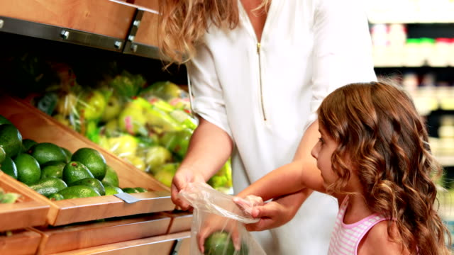 Mother and daughter picking out pepper in supermarket video
