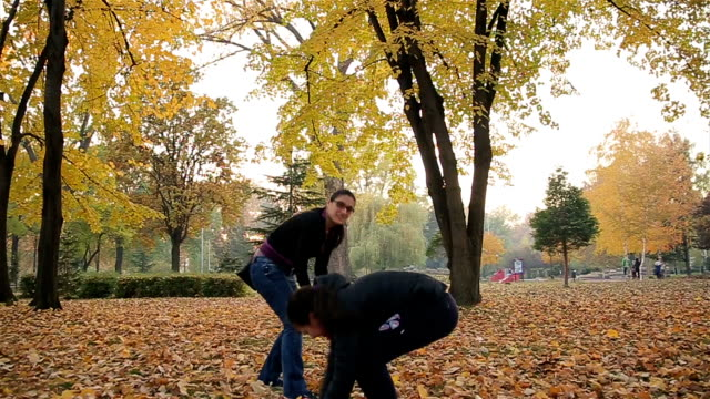 mother and daughter playing in the park with autumn leaves video