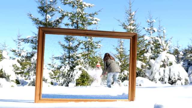 Mother and daughter playing in winter snow, frame in the foreground video