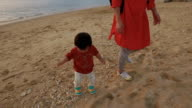 Mother and daughter playing on the beach. video