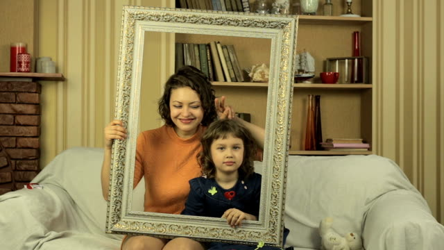 Mother and daughter posing with picture frame on the couch in the living room video