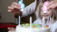 Mother and daughter preparing a birthday cake for father video