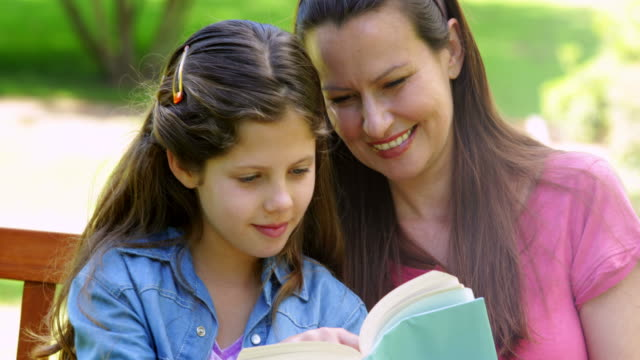 Mother and daughter reading together on a park bench video