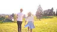 SLO MO Mother and daughter running with dandelion seeds video